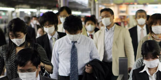 JAPAN - MAY 22:  Commuters wear masks at the Osaka Station in Osaka City, Japan, on Friday, May 22, 2009. Swine flu spread to more people in Japan as the government moderated its response to the outbreak, and claimed another life in the U.S. in a scourge that's reached 41 nations.  (Photo by Tomohiro Ohsumi/Bloomberg via Getty Images)