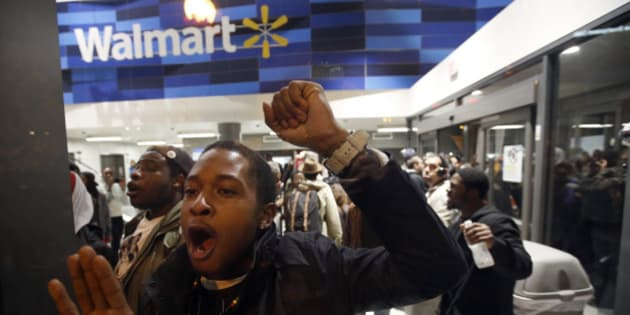 Protestors bang on the glass as they storm a Walmart in Washington, Tuesday, Nov. 25, 2014. A grand jury in Ferguson, Mo., on Monday, Nov. 24th, 2014, declined to indict police officer Darren Wilson in the shooting death of Michael Brown, an unarmed African-American man. (AP Photo/Alex Brandon)