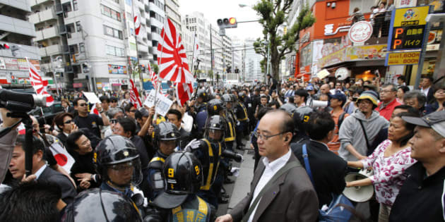 "In this photo taken Sunday, May 19, 2013, nationalist protesters with Japanese flags and Japan's naval ensign march through a Tokyo street to denounce ""privileges"" for Koreans residents in Japan as riot police line up along the street. Anti-Korean rallies have escalated this year and spread to other cities with Korean communities. In Tokyo's Shin-Okubo district, dotted with Korean restaurants and shops popular among South Korean pop-culture fans, hundreds of Zaitokukai members and supporters have called Koreans ""cockroaches,"" shouted ""Kill Koreans"" and threatened to ""throw them into the sea."" (AP Photo/Shizuo Kambayashi)"