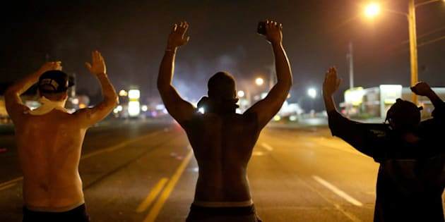 FERGUSON, MO - AUGUST 17:  Demonstrators raise their arms and chant, 'Hands up, Don't Shoot', as police clear them from the street as they protest the shooting death of Michael Brown on August 17, 2014 in Ferguson, Missouri. Police sprayed pepper spray, shot smoke, gas and flash grenades as violent outbreaks have taken place in Ferguson since the shooting death of Michael Brown by a Ferguson police officer on August 9th.  (Photo by Joe Raedle/Getty Images)