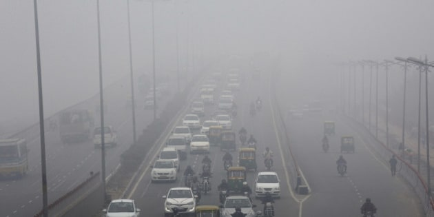 Traffic moves along a road shrouded in haze in New Delhi, India, on Monday, Jan. 20, 2014. India, China and Brazil, three of the largest developing nations, joined the U.S. in a list of the biggest historical contributors to global warming, according to a study by researchers in Canada. Photographer: Kuni Takahashi/Bloomberg via Getty Images