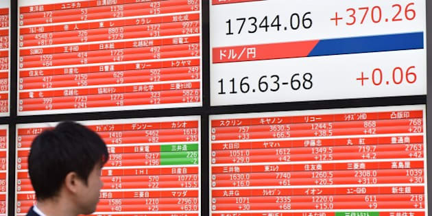 A pedestrian looks at a stock market share prices board in Tokyo on November 18, 2014. Tokyo stocks rose 2.18 percent on a weaker yen and bargain-hunting after tumbling a day earlier in response to data showing the Japanese economy had slumped into recession.  AFP PHOTO / KAZUHIRO NOGI        (Photo credit should read KAZUHIRO NOGI/AFP/Getty Images)