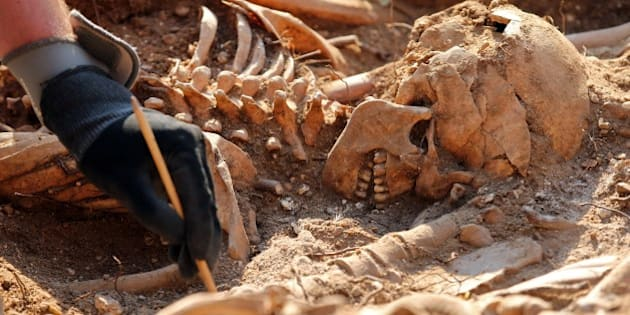 An employee exhumes on Mount Estepar near Burgos on July 24, 2014, the remains of people dumped in mass graves over the summer of 1936 during the Spanish Civil War. Work is expected to last two weeks, during which an estimated 90 to 100 corpses will be unearthed by 20 workers from the association Aranzadi Science Society, history students from Burgus University and members of the cordinating body for the recovery of historical memory. AFP PHOTO / CESAR MANSO        (Photo credit should read CESAR MANSO/AFP/Getty Images)