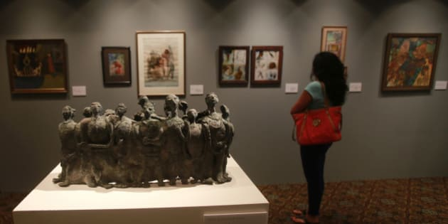 In this photo taken Dec. 16, 2013, a visitor looks at an art work during a media preview of Christie's first auction in India.Christie's holds its first art auction in India on Thursday, Dec. 19, 2013 aiming to tap into a budding market for prestige purchasing among the country's fast-growing ranks of millionaires despite an economic slowdown. While overall Indian growth has been stalling, the number of people worth $1 million or more is expanding and they show no signs of slowing their spending, fueling double-digit growth in the luxury market for the past five years. (AP Photo/Rafiq Maqbool)
