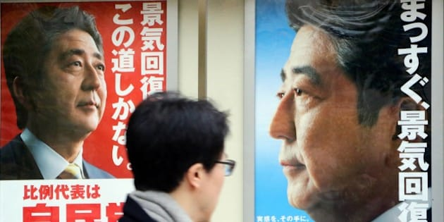 A man walks past posters of Japanese Prime Minister and ruling Liberal Democratic Party (LDP) leader Shinzo Abe displayed at the LDP headquarters in Tokyo on December 4, 2014. Abe's ruling party is set for a landslide win in the December 14 election, according to opinion polls.  AFP PHOTO / Yoshikazu TSUNO        (Photo credit should read YOSHIKAZU TSUNO/AFP/Getty Images)