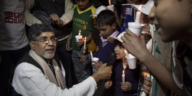 Indian children's rights activist Kailash Satyarthi holds a microphone for a child to speak during a candlelit vigil in New Delhi, India, Saturday, Nov. 22, 2014. Satyarthi and Malala Yousafzai of Pakistan jointly won the Nobel Peace Prize for 2014, for risking their lives to fight for children's rights. (AP Photo/Tsering Topgyal)
