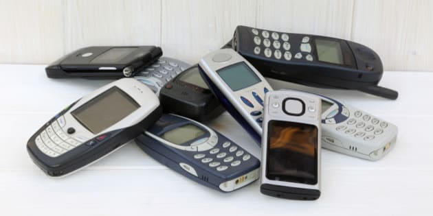 Nine outdated mobile phones stored in pile on shelf.