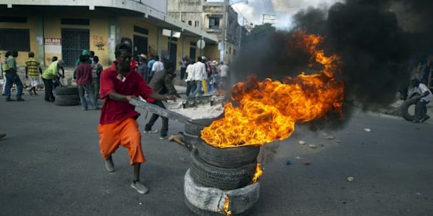Protesters block a street with burning tires and barricades in the center of Port-au-Prince on December 5, 2014. Protesters marched through the streets calling for the resignation of the Haitian leader Michel Martelly and the Prime Minister, Laurent Lamothe. In the center of the city the demonstrators protested in front of the National Palace and after blocked some streets nearby to the palace with burning tires and barricades.   AFP PHOTO/Hector RETAMAL        (Photo credit should read HECTOR RETAMAL/AFP/Getty Images)