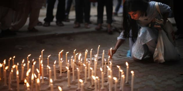 An activist places a candle on a pavement during a candle lit vigil to protest against the gang rape of two teenage girls, in New Delhi, India, Saturday, May 31, 2014. Police arrested a third suspect and hunted for two others Saturday in the gang rape and slaying of two teenage cousins found hanging from a tree in Katra village, in the northern Indian state of Uttar Pradesh, a case that has prompted national outrage. (AP Photo/Altaf Qadri)