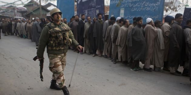 An Indian paramilitary soldiers walks past Kashmiri voters standing in queue outside a polling station during the first phase of voting to the Jammu and Kashmir state assembly elections in Lar, some 30 kilometers (19 miles) north of Srinagar, Indian controlled Kashmir, Tuesday, Nov. 25, 2014. The five phased voting is scheduled to be held till December 20 with the results expected on December 23. (AP Photo/ Dar Yasin)