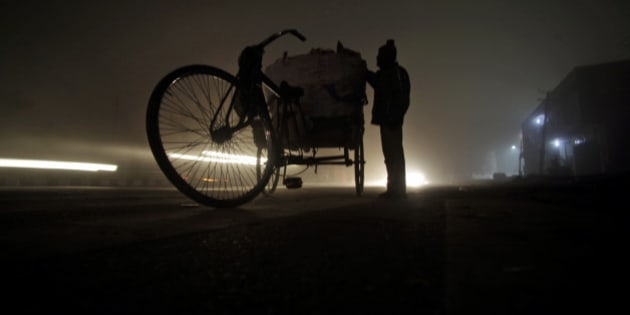 In this Thursday, Jan. 16, 2014 photo, an Indian rag picker works at a roadside enveloped in dense fog on a cold night in Jammu, India. Unabated cold wave and icy wind continue to throw normal life out of gear, disrupting rail, road and air traffic. (AP Photo/Channi Anand)