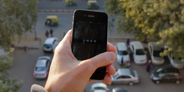 The Uber smartphone app, used to book taxis using its service, is pictured over a parking lot as auto-rickshaws (background) ply a road in the Indian capital New Delhi on December 7, 2014. An Uber taxi driver allegedly raped a 25-year-old passenger in the Indian capital before threatening to kill her, police said December 7, in a blow to the company's safety-conscious image. AFP PHOTO/TENGKU BAHAR        (Photo credit should read TENGKU BAHAR/AFP/Getty Images)