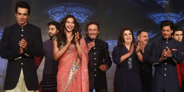 """From left to right, Bollywood actors Sonu Sood, Abhishek Bachchan, Deepika Padukone, Jackie Shroff, Director Farah Khan, Boman Irani, Shah Rukh Khan and Vivaan Shah applaud during a promotional event for their upcoming film """"Happy New Year"""" in Mumbai, India, Thursday, Aug. 14, 2014. The film is scheduled for release  Oct. 24. (AP Photo/Rafiq Maqbool)"""