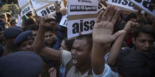Protestors from All India Students Association (AISA) demonstrate outside the Delhi Police headquarters after a taxi driver from the international cab-booking service Uber allegedly raped a young woman Friday in New Delhi, India, Sunday, Dec. 7, 2014. Official statistics say about 25,000 rapes are committed every year in India, a nation of 1.2 billion people. (AP Photo/Tsering Topgyal)