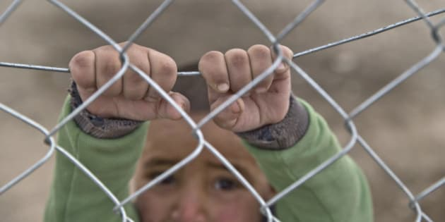 A Syrian Kurdish refugee child from the Kobani area, holds on to a fence at a camp in Suruc, on the Turkey-Syria border Sunday, Nov. 16, 2014. Kobani, also known as Ayn Arab, and its surrounding areas, has been under assault by extremists of the Islamic State group since mid-September and is being defended by Kurdish fighters. (AP Photo/Vadim Ghirda)