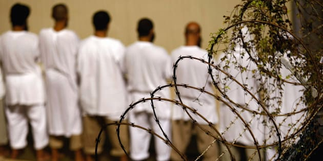 GUANTANAMO BAY, CUBA - OCTOBER 28: (EDITORS NOTE: Image has been reviewed by U.S. Military prior to transmission)  Detainees stand during an early morning Islamic prayer at the U.S. military prison for 'enemy combatants' on October 28, 2009 in Guantanamo Bay, Cuba. Although U.S. President Barack Obama pledged in his first executive order last January to close the infamous prison within a year's time, the government has been struggling to try the accused terrorists and to transfer them out ahead of the deadline. Military officials at the prison point to improved living standards and state of the art medical treatment available to detainees, but the facility's international reputation remains tied to the 'enhanced interrogation techniques' such as waterboarding employed under the Bush administration. (Photo by John Moore/Getty Images)