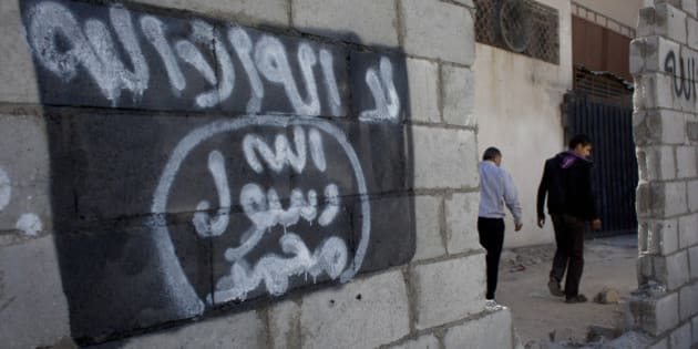 "In this photo taken Oct. 28, 2014, two Jordanian men walk past graffiti depicting the flag of the Islamic State group with Arabic that reads, ""There is only one God and Muhammad is his prophet,"" in the city of Ma'an, Jordan.  Local authorities quickly stripped away public signs of support for the Islamic State group in this desert town. Black flags have been removed from rooftops. Graffiti proclaiming the extremists' imminent victory have been whitewashed. But supporters of the Middle East's most radical extremist group are only laying low. (AP Photo/Nasser Nasser)"