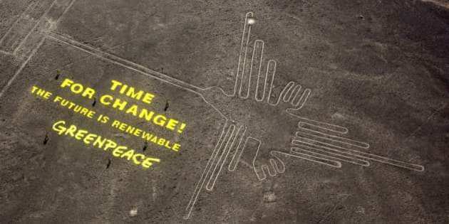 "Greenpeace activists stand next  to massive letters delivering the message ""Time for Change: The Future is Renewable"" next to the hummingbird geoglyph in Nazca in Peru, Monday, Dec. 8, 2014. Greenpeace activists from Brazil, Argentina, Chile, Spain, Germany, Italy and Austria displayed the message, which can be viewed from the sky, during the climate talks in Peru, to honor the Nazca people, whose ancient geoglyphs are one of the country's cultural landmarks. (AP Photo/Rodrigo Abd)"