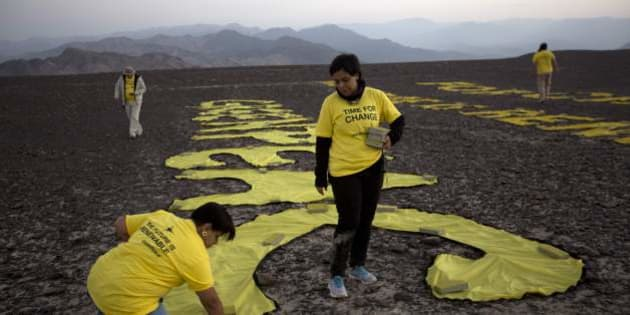 "Greenpeace activists arrange the letters delivering the message ""Time for Change: The Future is Renewable"" next to the hummingbird geoglyph in Nazca, Peru, Monday, Dec. 8, 2014. Greenpeace activists from Brazil, Argentina, Chile, Spain, Germany, Italy and Austria displayed the message, which can be viewed from the sky, during the climate talks in Peru, to honor the Nazca people, whose ancient geoglyphs are one of the countries cultural landmarks. (AP Photo/Rodrigo Abd)"