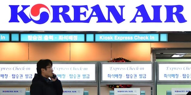 A man talks over his mobile phone in front of the logo of Korean Air at Gimpo airport in Seoul on December 9, 2014. Korean Air apologised as it faced a media backlash over the daughter of the airline's CEO, who had a chief purser ejected from a plane in a furious reaction to being incorrectly served some macadamia nuts. AFP PHOTO / JUNG YEON-JE        (Photo credit should read JUNG YEON-JE/AFP/Getty Images)