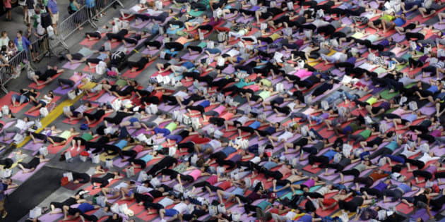 Thousands of New Yorkers are marking the first day of summer by practicing yoga in Times Square, during the 12th annual Solstice in Times Square, sponsored by the Times Square Alliance and Athleta, Gap Inc.'s exercise-wear brand, Saturday, June 21, 2014. (AP Photo/Richard Drew)