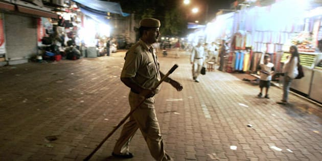 New Delhi, INDIA:  A Delhi Policeman patrols a night market as the the Indian capital was put on a high security alert following a serie of bomb blasts in India's financial capital of Mumbai, in New Delhi, 11 July 2006.  Seven explosions ripped through commuter trains during evening rush hour in India's financial capital Mumbai, killing up to 90 people in what police quickly called a terrorist attack.  AFP PHOTO/ MANAN VATSYAYANA   (Photo credit should read Manan Vatsyayana/AFP/Getty Images)