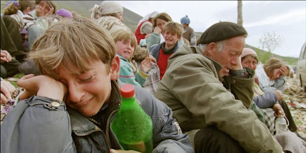 Kosovo Albanian refugees cry 15 April 1999 at the border between Yugoslavia and Albania near the northern town of Kukes. Some 6,600 Kosovo Albanian refugee entered Albania and Macedonia today according to figures released by the United Nations High Commissioner for Refugees.        (Photo credit should read JOEL ROBINE/AFP/GettyImages)
