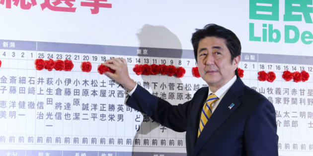 Shinzo Abe, Japan's prime minister and president of the Liberal Democratic Party (LDP), places a red paper rose on a LDP candidate's name to indicate a lower house election victory, at the party's headquarters in Tokyo, Japan, on Sunday, Dec. 14, 2014. Abe's ruling coalition won Japan's general election, according to an NHK exit poll, which also indicates the bloc may maintain its two-thirds majority in the lower house. Photographer: Tomohiro Ohsumi/Bloomberg via Getty Images