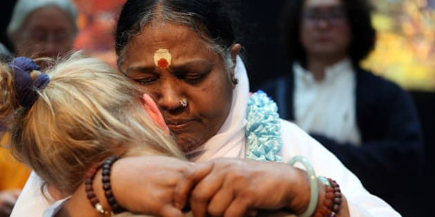 BERLIN, GERMANY - NOVEMBER 12:  Mata Amritanandamayi Devi, primarily known simply as Amma ('Mother'), the hugging saint, hugs a devotee in the event hall Arena, on November 12, 2014 in Berlin, Germany. Amritanandamayi, an Indian guru, has hugged over 33 million people around the world, her own form of a Hindu blessing known as a Darshan, a gesture she believes 'can help to awaken dormant spiritual energy within them.' Amma also runs a group of global charities, known as Embracing the World.  (Photo by Adam Berry/Getty Images)