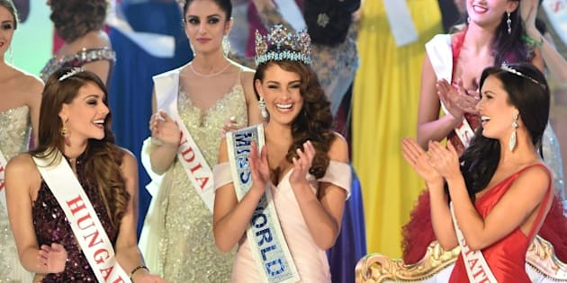 Miss South Africa and the 2014 Miss World, Rolene Strauss (C), dances with first runner up Miss Hungary Edina Kulcsar (L) and second runner up Miss United States Elizabeth Safrit (R) during the grand final of the Miss World 2014 pageant at the Excel London ICC Auditorium in London on December 14, 2014. AFP PHOTO / LEON NEAL        (Photo credit should read LEON NEAL/AFP/Getty Images)