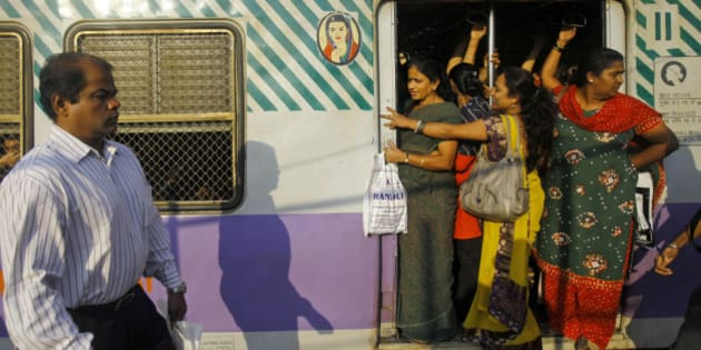 Indian women stand on a door of the ladies compartment of a train as they travel to work early morning in Mumbai, India, Thursday, Jan. 10, 2013. Police badly beat the five suspects arrested in the brutal gang rape and killing of a young woman on a New Delhi bus, the lawyer for one of the men said Thursday, accusing authorities of tampering with evidence in the case that has transfixed India. (AP Photo/Rafiq Maqbool)