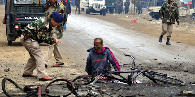 Indian police personnel (L) talk to an injured person at the bomb blast site in Imphal, the capital city of India's northeastern state of Manipur on November 30, 2011. A bomb in the northeastern Indian state of Manipur killed a man suspected of planting the explosives, police said, days ahead of a visit by the prime minister. AFP PHOTO/STR (Photo credit should read STRDEL/AFP/Getty Images)