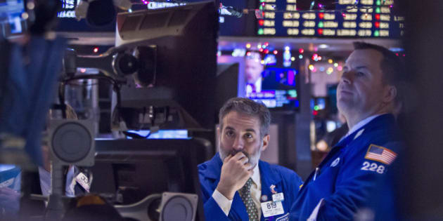 Barclays traders Anthony Rinaldi, left, and Michael McDonnell monitor stock information at their trading bay at the New York Stock Exchange during early trading, Monday, Dec. 15, 2014, in New York.  U.S. stocks opened broadly higher Monday following the biggest weekly losses in two and a half years.  (AP Photo/Bebeto Matthews)