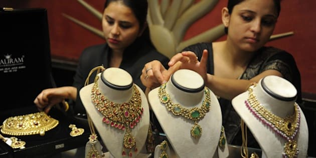 Indian employees display gold jewellery at a jewellery store to mark Dhanteras in Amritsar on October 21, 2014. Dhanteras, which happens two days before the Hindu festival Diwali, is seen as an auspicious day to make purchases. AFP PHOTO/NARINDER NANU        (Photo credit should read NARINDER NANU/AFP/Getty Images)