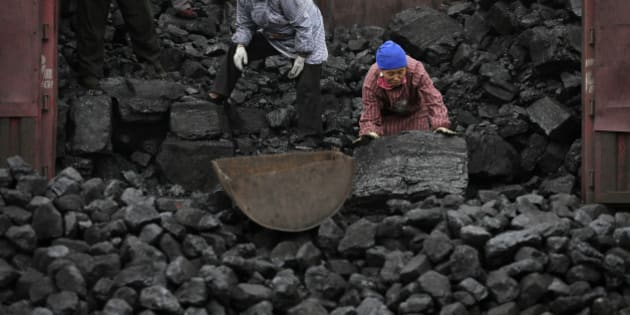 In this Nov. 27, 2014 photo, workers load coal from a truck to a process station in Tangxian in China's Hebei province. Just a few dozen miles from the capital of Beijing, in Hebei province, coal use has long been a way of life here, with countless house-sized mounds of it dotting the forest floor. Yet the soot-covered residents of Tang County said they see change coming as Chinese leaders pledge to cut back on the kind of rampant coal use that has made this country the world's biggest emitter of greenhouse gases. (AP Photo/Andy Wong)