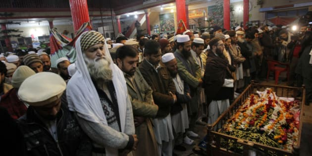 Mourners and relatives of Pakistani teacher, Saeed Khan, a victim of a Taliban attack in a school, pray around his body, during his funeral procession in Peshawar, Pakistan, Tuesday, Dec. 16, 2014. Taliban gunmen stormed a military-run school in the northwestern Pakistani city of Peshawar on Tuesday, killing at least 100 people, mostly children, before Pakistani officials declared a military operation to clear the school over. (AP Photo/Mohammad Sajjad)