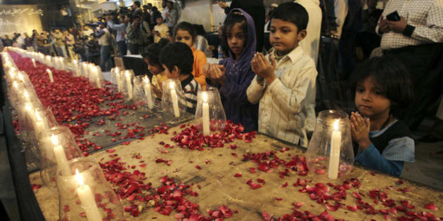 Pakistani children, chant prayers, during a candle light vigil for the victims of a Taliban attack on a school in Peshawar, organized by supporters of the Mutahida Qaumi Movement (MQM), in Karachi, Pakistan, Tuesday, Dec. 16, 2014. Taliban gunmen stormed a military-run school in the northwestern Pakistani city of Peshawar on Tuesday, killing more than 100, officials said, in the highest-profile militant attack to hit the troubled region in months. (AP Photo/Fareed Khan)