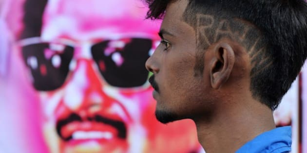 A young fan of Indian film actor Rajinikant, sporting the star's name in his hair-do, arrives at a movie theatre in Bangalore on December 12, 2014 on the occasion of the release of his movie 'Linga' which coincides with Rajinikant's 64th birthday. The movie is being simultaneously released on 5000 screens worldwide and was made with a budget of 125 crore rupees (200 million US dollars).  AFP PHOTO/Manjunath KIRAN        (Photo credit should read Manjunath Kiran/AFP/Getty Images)