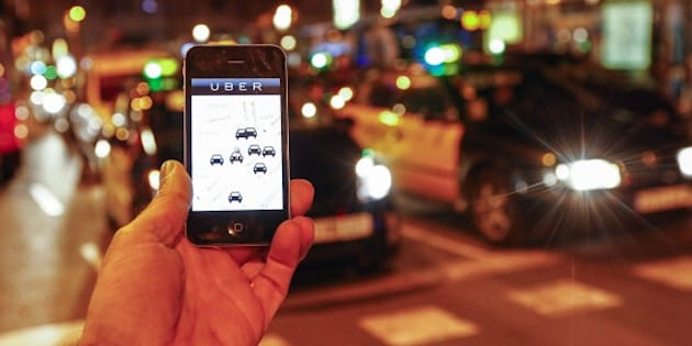 The Uber app is seen on a smartphone past cabs passing on Paseo de Gracia in Barcelona, on December 9, 2014. A judge on December 9, 2014 banned the popular smartphone taxi service Uber from operating in Spain, court officials said, following similar prohibition action in several other countries.     AFP PHOTO/ QUIQUE GARCIA        (Photo credit should read QUIQUE GARCIA/AFP/Getty Images)