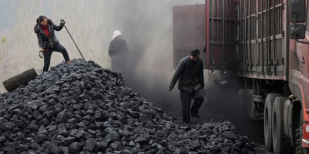 In this Nov. 27, 2014 photo, workers load coal from a truck at a process station for sale in Tangxian in China's Hebei province. Just a few dozen miles from the capital of Beijing, in Hebei province, coal use has long been a way of life here, with countless house-sized mounds of it dotting the forest floor. Yet the soot-covered residents of Tang County said they see change coming as Chinese leaders pledge to cut back on the kind of rampant coal use that has made this country the world's biggest emitter of greenhouse gases. (AP Photo/Andy Wong)
