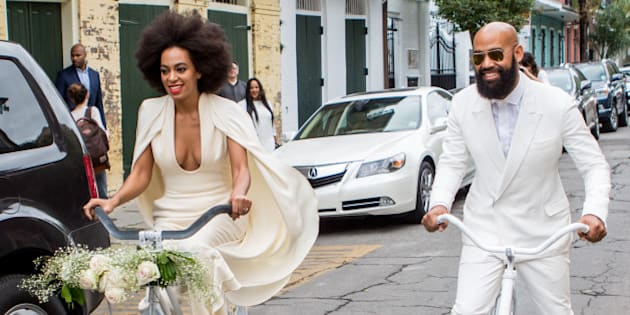 NEW ORLEANS, LA - NOVEMBER 16:  Musician Solange Knowles (wearing a pre-ceremony ensemble by Stephane Rolland) and her fiance, music video director Alan Ferguson, ride bicycles on the streets of the French Quarter en route to their wedding ceremony at the Marigny Opera House on November 16, 2014 in New Orleans, Louisiana.  (Photo by Josh Brasted/WireImage)