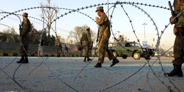 Pakistan Army soldiers cordon off the area of a suicide bombing in Peshawar, Pakistan on Friday, Nov. 13, 2009. A suicide car bomb devastated Pakistan's main spy agency building in the northwest Friday, killing at least 7 people and striking at the heart of the institution overseeing much of the country's anti-terror campaign.(AP Photo/Mohammad Sajjad)