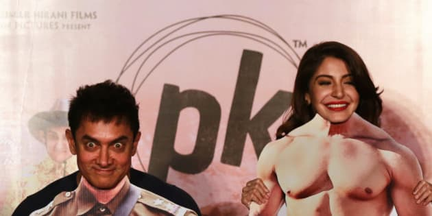"""Bollywood actors Aamir Khan, left, and Anushka Sharma pose with movie character cut-outs during the teaser launch of their upcoming film """"PK"""" in Mumbai, India, Thursday, Oct. 23, 2014. The movie is scheduled for release on Dec. 19. (AP Photo/Rafiq Maqbool)"""