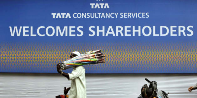 An umbrella seller walks in front of Tata Consultancy Services signboard on the day of its annual general meeting in Mumbai, India, Friday, June 29, 2012. (AP Photo/Rajanish Kakade)