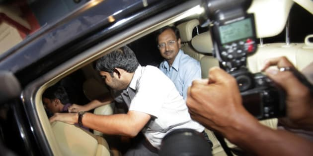 Satyam Computer Services Ltd. founder B. Ramalinga Raju, center, looks out from inside a car after he was released from Chanchalguda jail on being granted bail by the Supreme Court after he spent two years and eight months in the jail in Hyderabad, India, Saturday, Nov. 5, 2011. Raju, founder of the company that was once India's fourth largest software services company, confessed in January 2009 to inflating company assets by US$1.5 billion, a number government investigators later said was understated by at least US$1 billion. (AP Photo/Mahesh Kumar A)
