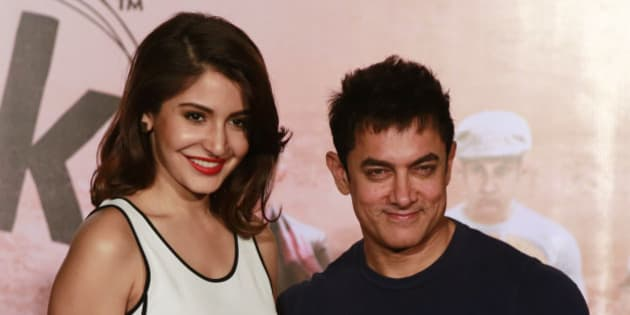 """Bollywood actors Aamir Khan, right, and Anushka Sharma pose for photographs during the teaser launch of their upcoming film """"PK"""" in Mumbai, India, Thursday, Oct 23, 2014. The movie is scheduled for release on Dec. 19. (AP Photo/Rafiq Maqbool)"""