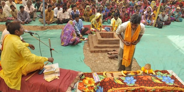 An Indian tribesperson (R, foreground) participates in a conversion ritual of some 200 Christians into Hinduism, at Aranai Village in Valsad district of Gujarat state, some 350 kms from Ahmedabad, on December 20, 2014. Hardline Hindu groups came under fire December 21 after some 200 Christians were converted in the Indian prime minister's home state, amid increasing concern at the right-wing government's perceived pro-Hindu tilt. AFP PHOTO / STR        (Photo credit should read STRDEL/AFP/Getty Images)