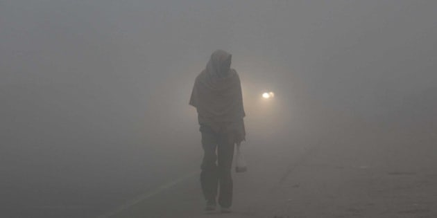 JAMMU, INDIA - DECEMBER 18: A man wrapped in warm clothes, moved through a fog covered road during a cold and foggy morning on December 18, 2014 in Jammu, India. Fog and mist continued to affect normal life and vehicular traffic across the state despite the mercury rose to one to two degree C at many places last night, the official said. The MeT department has forecast fresh Western Disturbance (WD) would affect the state from tomorrow resulting into rainfall or snowfall at few places. (Photo by Nitin Kanotra/Hindustan Times via Getty Images)