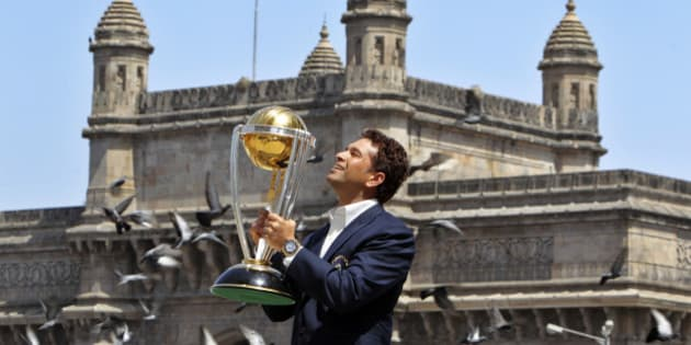 India's Sachin Tendulkar poses with the trophy after winning the Cricket World Cup final match against Sri Lanka in the backdrop of the Gateway of India monument in Mumbai, India, Sunday, April 3, 2011. (AP Photo/Gurinder Osan)