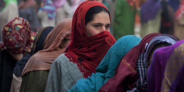 Kashmiri women stand in a queue to cast their votes during the fourth phase polling of the Jammu and Kashmir state elections on the outskirts of Srinagar, Indian controlled Kashmir, Sunday, Dec. 14, 2014. The elections are being held in five stages to allow government forces to better guard against any violence or anti-India protests. Results are due Dec. 23. (AP Photo//Dar Yasin)
